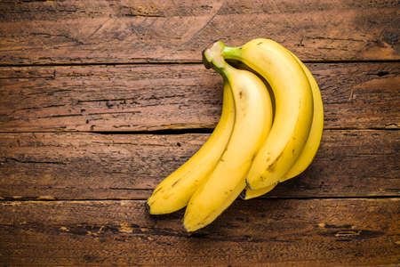 Top view fresh organic bananas on wooden table top Imagens