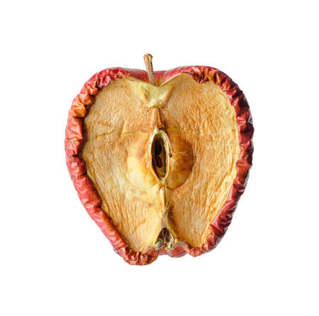 Rotten apple cut in half, aging or disease concept Фото со стока