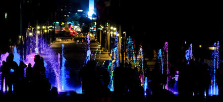 Silhouettes of people walking and playing in a colorful illuminated fountain at night Фото со стока