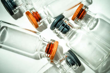 Pile of empty vaccine bottles, closeup seen from above