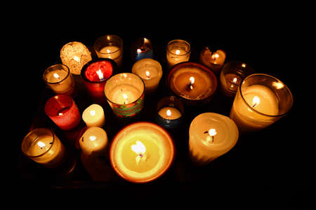 Many candles of different sizes and styles in the dark