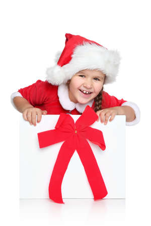 cloath: Portrait of happy little girl in Santa hat looks out of Christmas gift box, on a white background