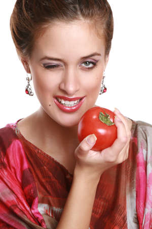 The fashionable brunette with a juicy, red tomato in hands