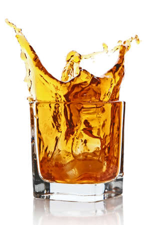 whisky: Glass with splashing whisky drink  Isolated on a white background