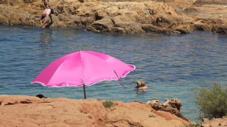 Pink sunshade on the rocks and bathers enjoying in the background Foto de archivo