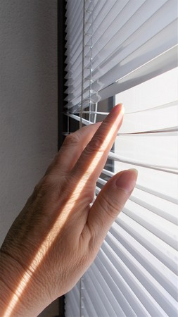 Line of sunlight in a woman's hand that separates the slats of a blind to look outside