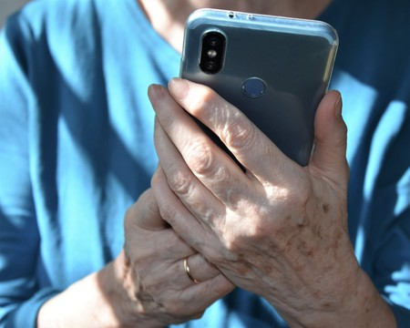 Hands of an old woman using a smartphone