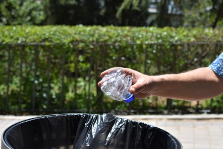 A male hand throws an used plastic bottle into the trash