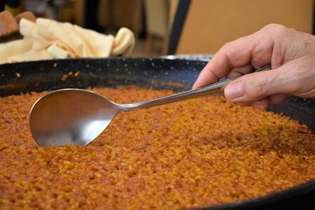 A man serves a garnish of rice made in paella with a ladle