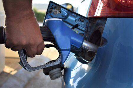 Een mannenhand drukt een brandstofpompmondstuk in de tank om deze te vullen