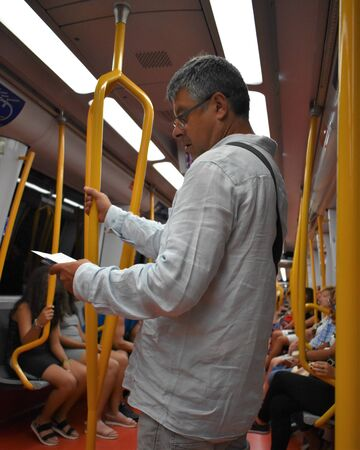 A passenger reads during his journey on the subway