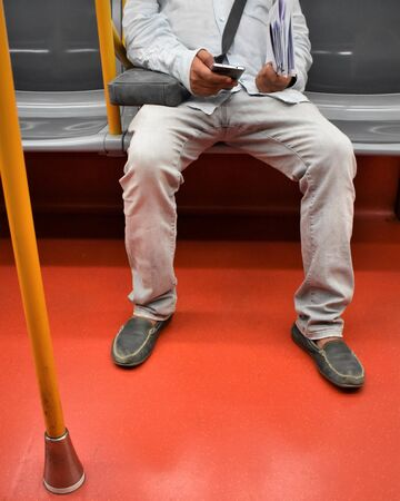 Passenger sitting during a subway ride using his smartphone