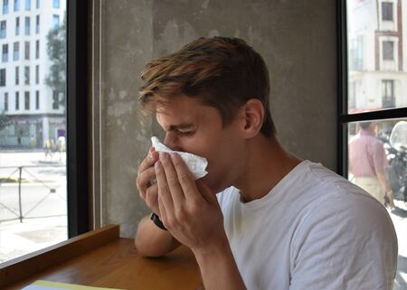 A young man suffers symptoms of a cold, flu or allergy, and blows his nose in a tissue