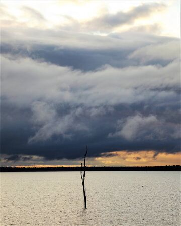 Stormy sky over a silvery lake at sunset 스톡 콘텐츠