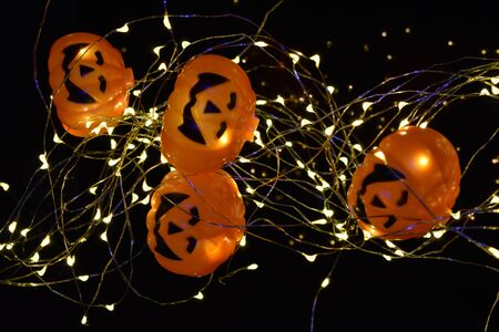 Halloween lights with several smiling pumpkins hanging on