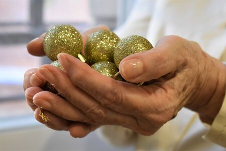 The hands of an old woman hold a set of Christmas balls to place on the fir