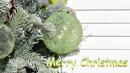 Christmas greeting with snow-covered fir branches, decorative balls, and space for text