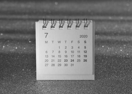 Spiral notebook type calendar showing the July 2020 page on a blurred silver background