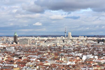 Aerial panorama of the Madrid (Spain) skyline on a cloudy day with the roofs and domes of the old part of the city in the foreground and Columbus tower and