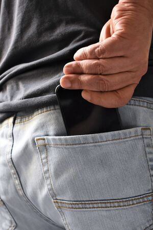 A male hand takes out (or keeps) a smartphone from the back pocket of his jeans 免版税图像