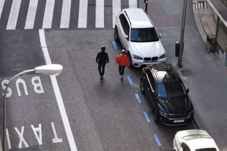 05-02-2020 Madrid, Spain. Aerial view of a Madrid downtown street without traffic during the confinement due to coronavirus with two people walking along.