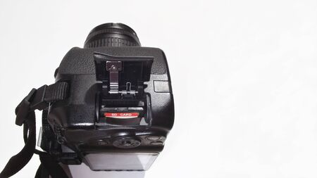 Memory SD flash card inserted into a digital reflex camera (DRLS). Kit image isolated on light gray background with copy space Imagens