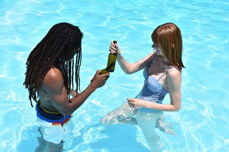 Couple multiethnique d'homme africain avec des dreadlocks et une fille rousse dans une piscine grillant avec des bouteilles de bière. Concept de plaisir et de détente estival