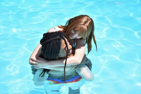 Multiethnic couple of african guy with dreadlocks and redhead girl having fun in a swimming pool. Summery enjoyment and relaxation concept. Stock fotó