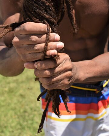 Foreground of the hands of an African guy just out of a pool squeezing the water out of his dreadlocks.