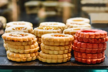 Close-up of a tray of layered flower-shaped butter cookies of different flavors filled with jam. Unhealthy eating concept