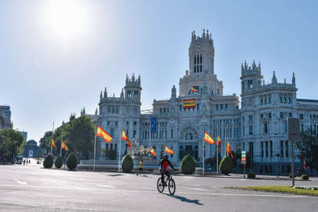 May 17 2020 Madrid, Spain Cibeles square without traffic due the epidemic circled by Spain flags at half mast in mourning for the coronavirus deads. The building's flag sais: thank you I stay at home Редакционное