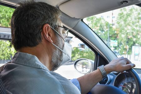 A middle-aged bearded man wearing a respiratory protection mask drives his car down Street leaving the city. Protection against air pollution. Concept of