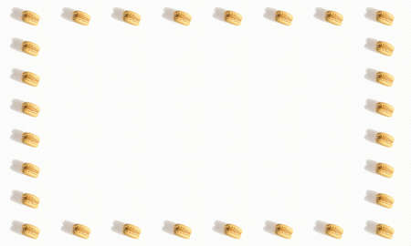 Twenty eight vanilla and caramel macarons placed forming a frame on a white soft striped background, with copy space.