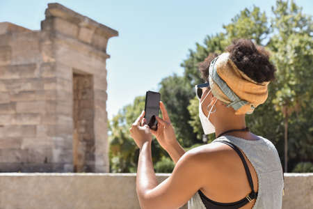 A young african origin woman wearing a face mask she uses her mobile phone to take a picture during a tourist excursion, on a blurred monumental background. Safe tourism in pandemic times.