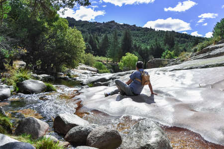 """Landscape with mountain stream and hiker sitting on a stone slope, enjoying the views. """"Sierra de Guadarrama"""" National Park, Madrid, Spain Banque d'images"""