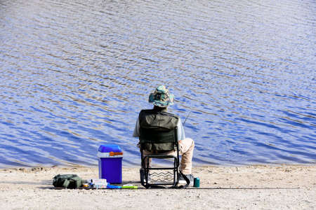 Back foreground of a sitting man angling on the shore of a lake with his spare rod and tackle