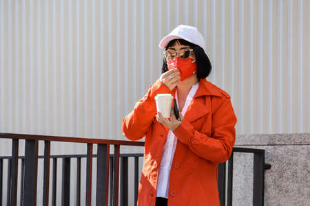 A young woman holds her mobile phone and a paper cup in her hand while removing her face mask to drink. 스톡 콘텐츠