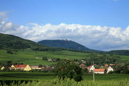 haut: Haut Koenigsbourg castle on peak of Vosges. Vineyards and small village in the valley. Alsace, France. Stock Photo