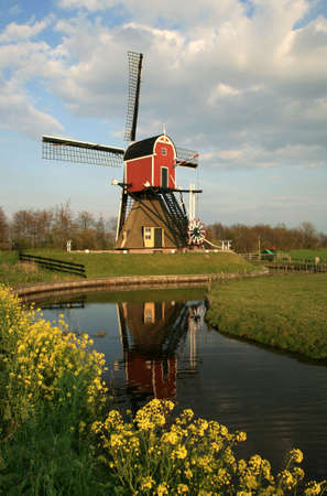 Old pump traditional Dutch windmill on meadow, Netherlands Stock Photo