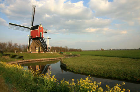 reverberation: Old pump traditional Dutch windmill on meadow, Netherlands Stock Photo