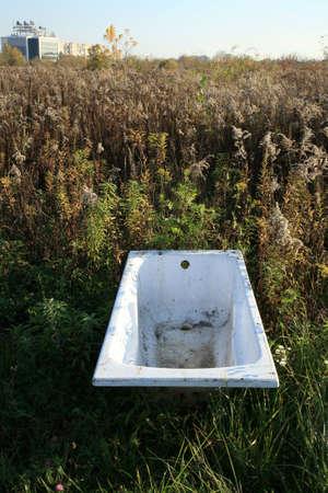 periferia: Vasca da bagno gettato sul prato - della civilt� rifiuti - minaccia per l'ambiente naturale. Espansione di un uomo. Devastazione dell'ambiente naturale.