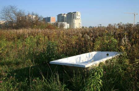 periferia: Vasca da bagno gettato sul prato - rifiuti di civilt� - minaccia per l'ambiente naturale. Ampliamento del uomo. Devastazione dell'ambiente naturale.
