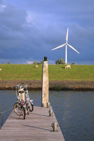 Eco-friendly means of transport and renewable energy. Bicycles above the canal and modern windmill by sunset. Environmental protection.