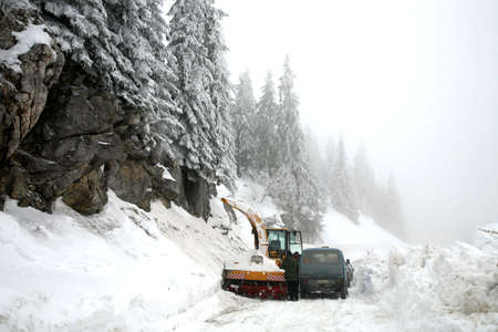 Snowplow in action on rural snow covered road. Winter in Balkans Mountain - Kosovo photo