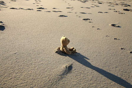 needless: Lonely teddy bear lost on the beach. Left childrens toy.