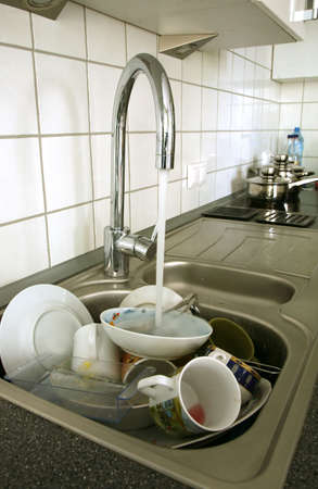 Pile of dirty dishes in the metal sink and pouring tap water. Kitchen after breakfast. Stock Photo - 3896251