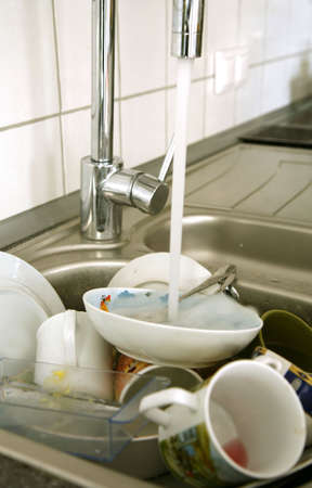 Pile of dirty dishes in the metal sink and pouring tap water. Kitchen after breakfast. Stock Photo - 3896244