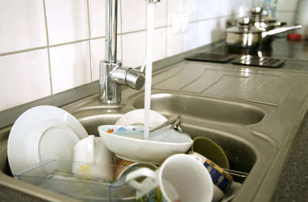messy kitchen: Pile of dirty dishes in the metal sink and pouring tap water. Kitchen after breakfast.