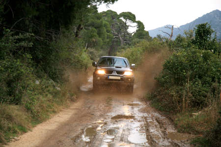 A car sprays mud. Surmounting the wild area. Ride on the of-road car. 4x4 off-roading in Croatia.