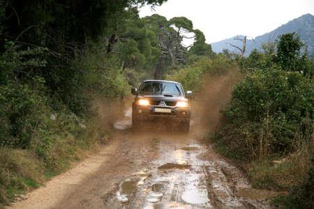 mud slide: A car sprays mud. Surmounting the wild area. Ride on the of-road car. 4x4 off-roading in Croatia.